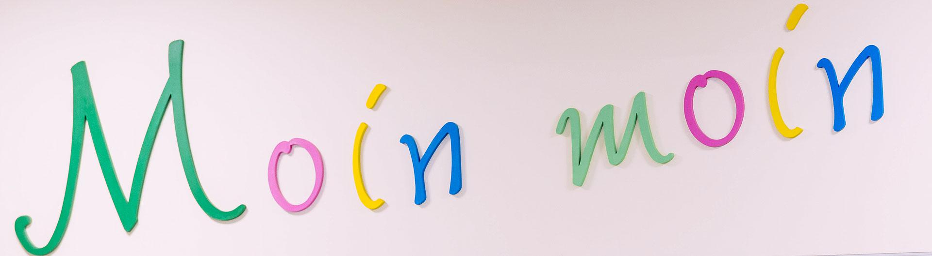 """Das Bild zeigt einen Schriftzug aus bunten Buchstaben: Moin moin"""". Dieser Schriftzug ist über der Essensausgabe der Mensa angebracht."""