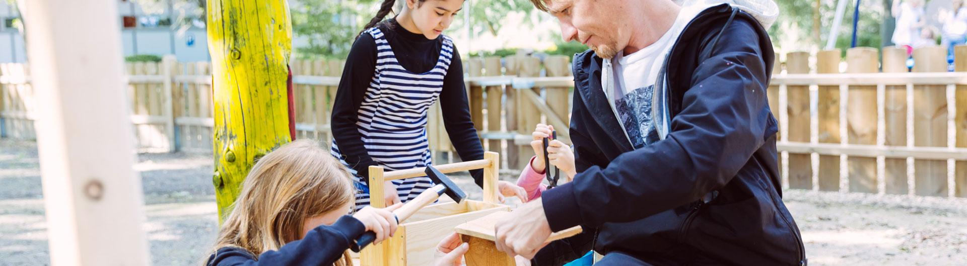 Ein Betreuer baut mit zwei Kindern aus Holz Nistkästen.