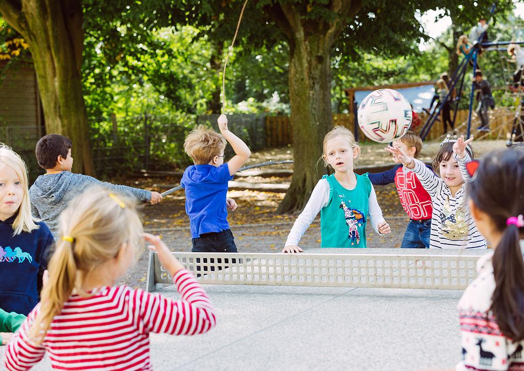 Das Bild zeigt eine Tischtennisplatte der Schule Lehmkuhle. Dort spielen einige Kinder und werfen sich einen Fußball zu.