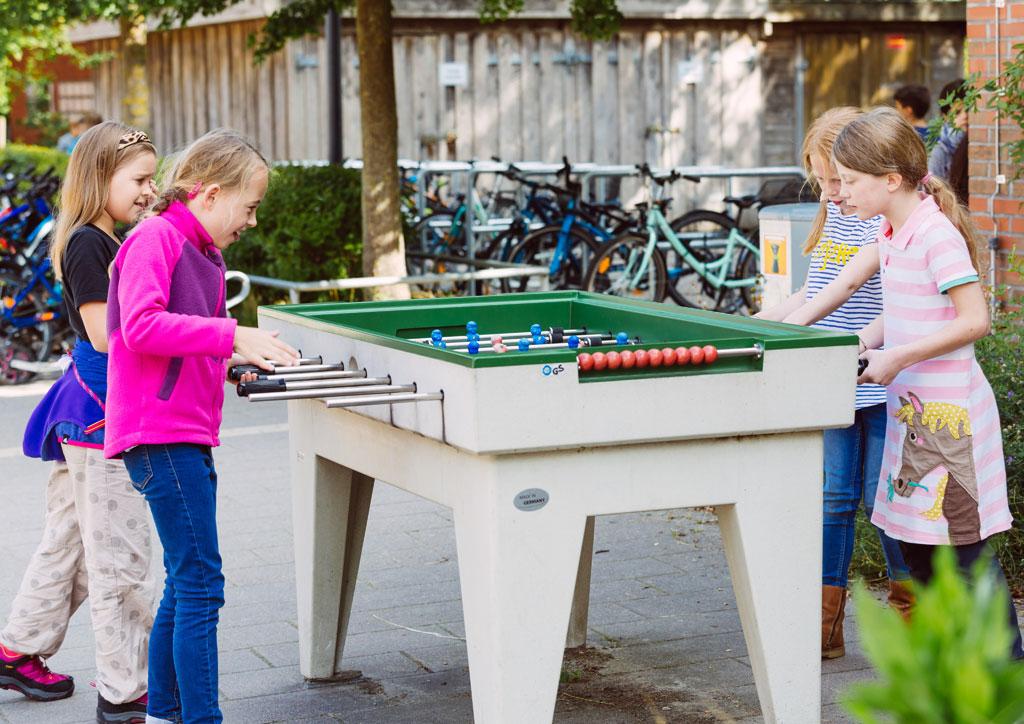 Das Bild zeigt einen Tischfußball auf dem Schulhof der Schule Lehmkuhle. 4 Mädchen haben gerade ein Tisch-Fußball-Match.