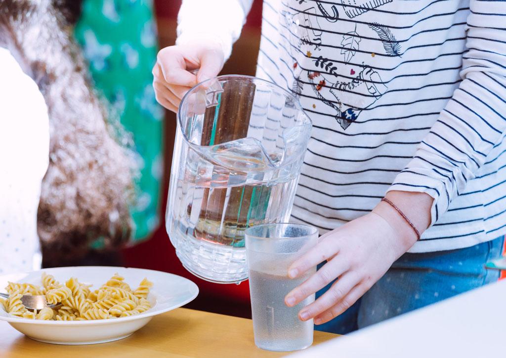 Das Bild zeigt einen Teller mit Nudeln und ein Mädchen, dass ich gerade aus einer Karaffe Wasser in ein Glas gießt. Hier ist gerade Mittagspause in der Mensa des neuen Schulgebäudes.