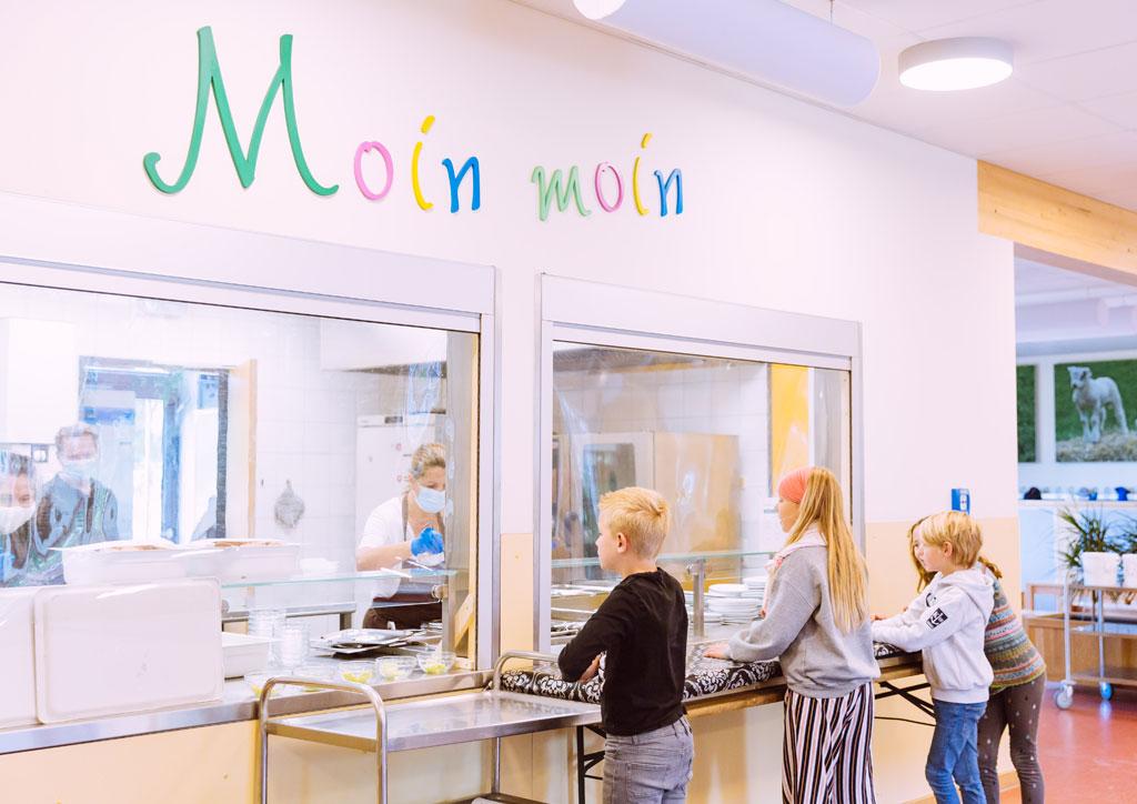 Das Bild zeigt die Mensa der Schule Lehmkuhle. Einige Kinder warten auf ihr Essen an der Essensausgabe.