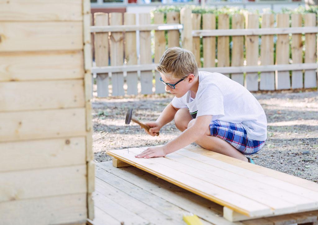 Das Bild zeigt einen Jungen, der mit einem Hammer einen Nagel in ein Brett nagelt. Die Kinder haben in der Ganztagsbetreuung die Möglichkeit viel mit Holz zu bauen.