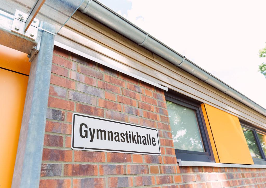 """Das Bild zeigt einen Teil des neuen Schulgebäudes der Schule Lehmkuhle. An der Wand ist ein Schild mit der Aufschrift """"Gymnastikhalle"""" angebracht. Dort befindet sich die neue Turnhalle."""