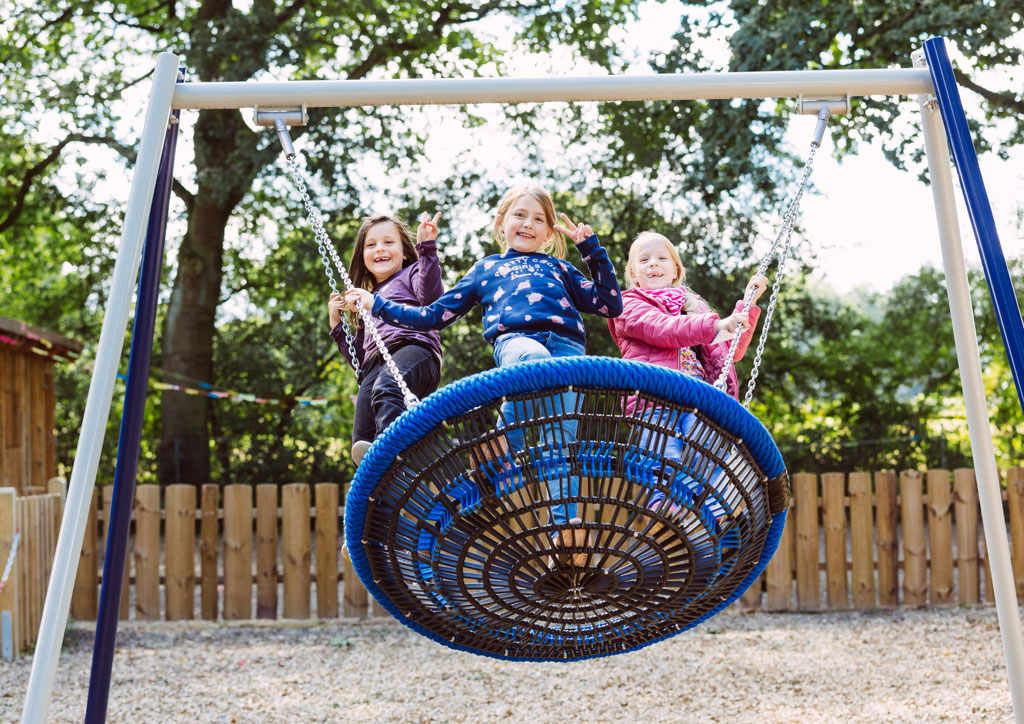 Das Bild zeigt eine große Nestschaukel in der sich drei Mädchen befinden, schaukeln und in die Kamera lachen.