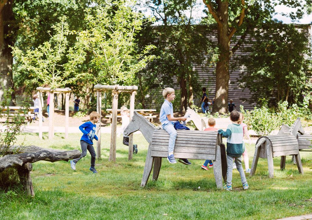 Das Bild zeigt einen Teil des Spielbereichs draußen auf dem Schulhof der Schule Lehmkuhle. Davor befinden sich mehrere große Holzpferde und spielende Kinder.