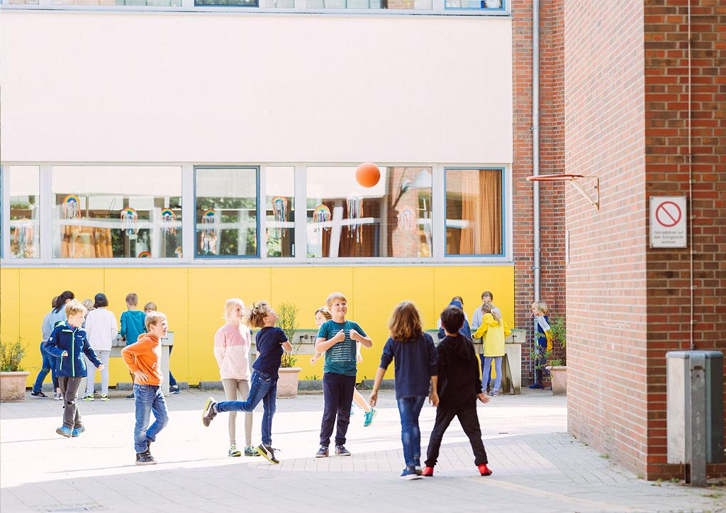 Das Bild zeigt spielende Kinder auf dem Schulhof der Schule Lehmkuhle.