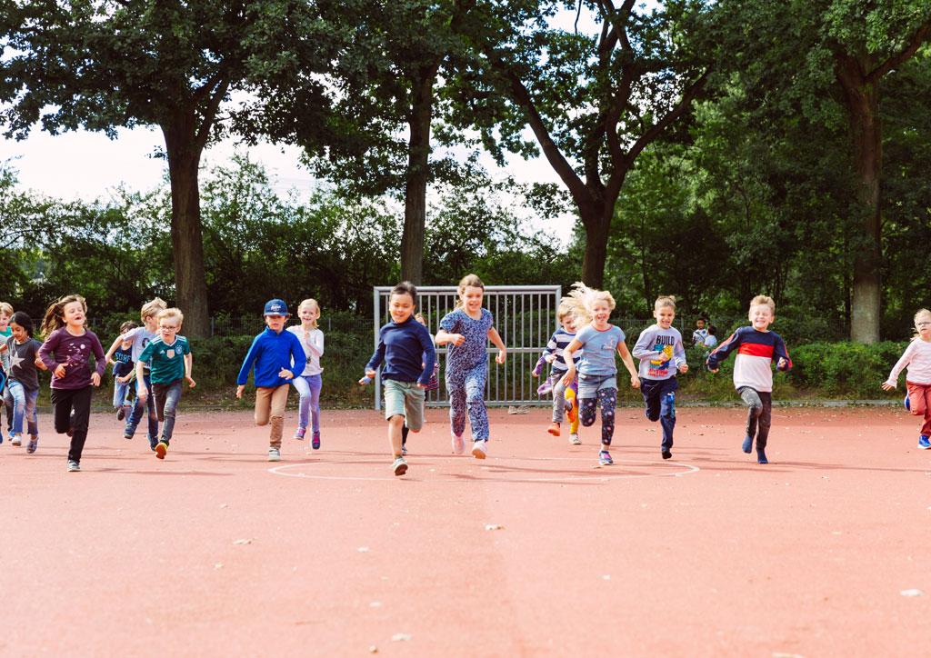 Das Bild zeigt einen Teil des Fußballplatzes der Schule Lehmkuhle. Es rennen ganz viele Kinder der Fotografin entgegen.