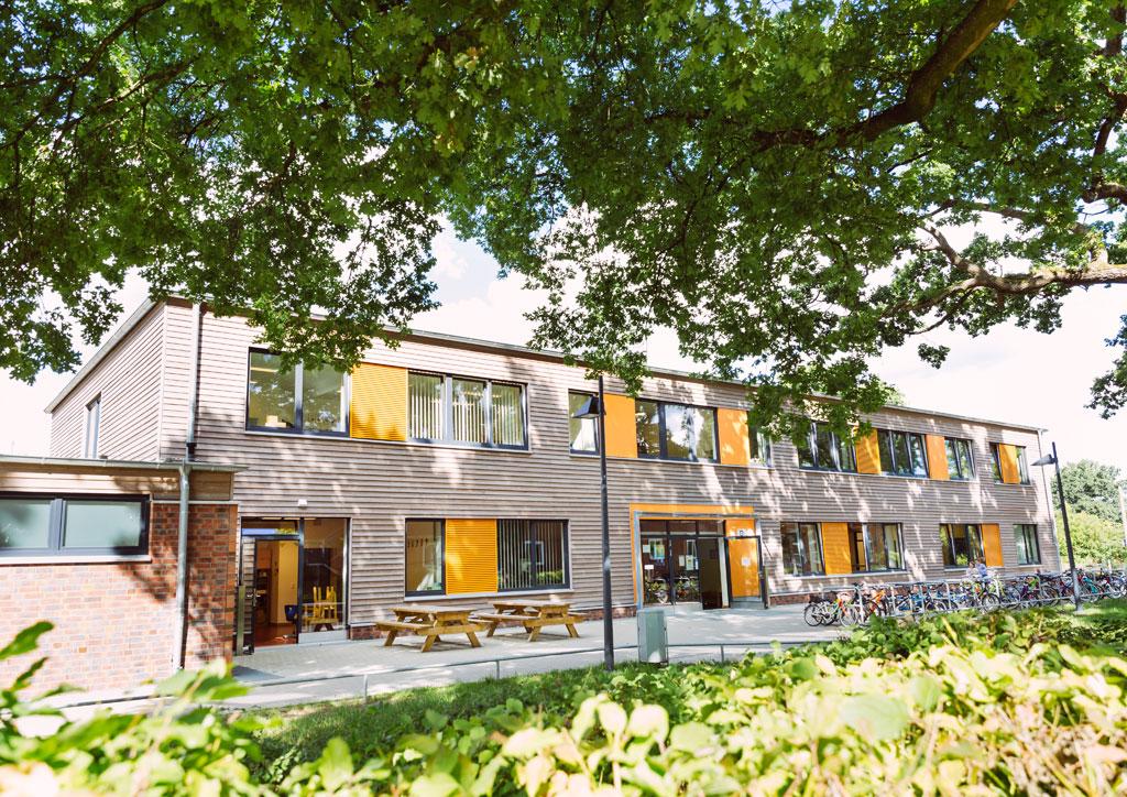 Das Bild zeigt das neue Schulgebäude der Schule Lehmkuhle. Davor stehen zwei Holzsitzbänke und Fahrradständer für viele Fahrräder.