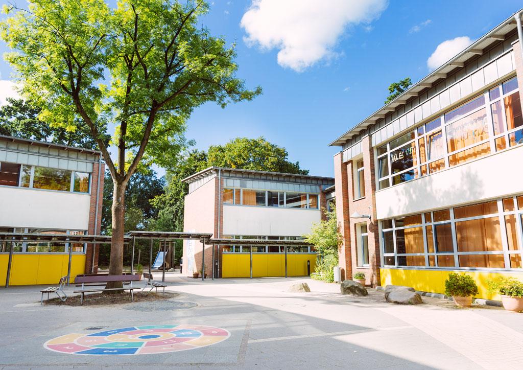 Das Bild zeigt den Schulhof der Schule Lehmkuhle. Auf dem Steinboden ist eine bunte Schnecke mit Zahlen aufgemalt zum Hüpfen.