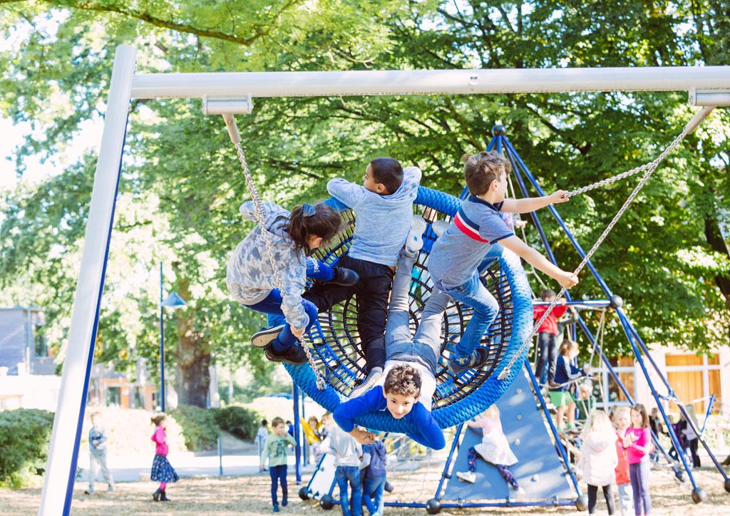 Das Bild zeigt eine große Nestschaukel in der sich vier Kinder befinden, die sehr hoch schaukeln und viel Spaß dabei haben.