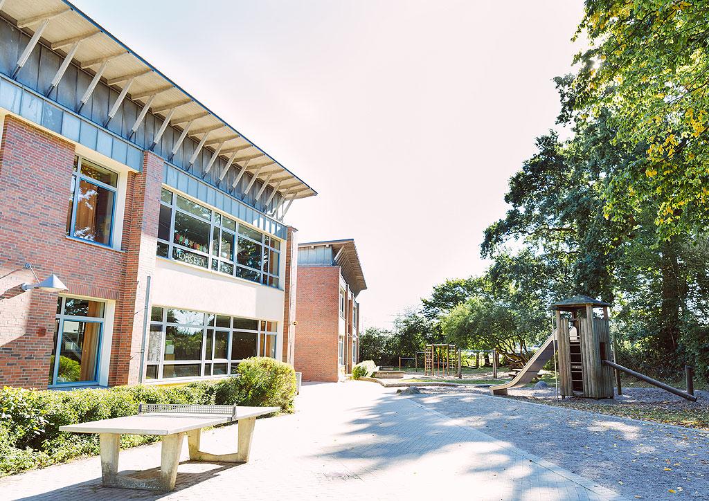 Das Bild zeigt den Schulhof der Schule Lehmkuhle mit einem Tischtennistisch und dem Rutschturm im großen Sandkasten.