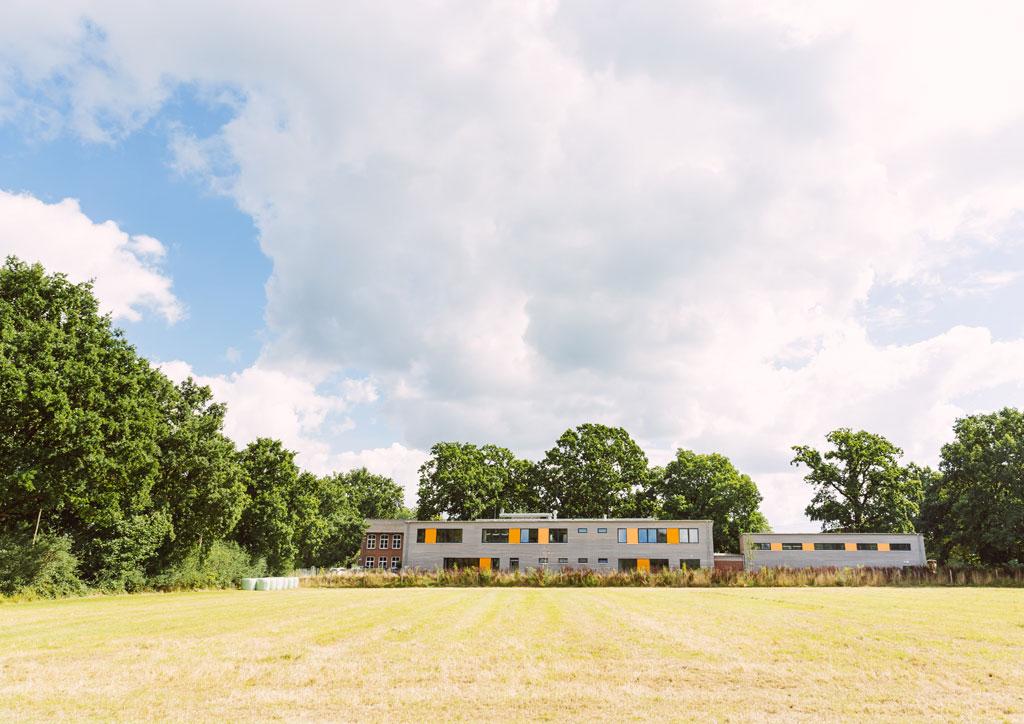 Das Bild zeigt das neue Schulgebäude der Schule Lehmkuhle. Davor befindet sich eine große Wiese.
