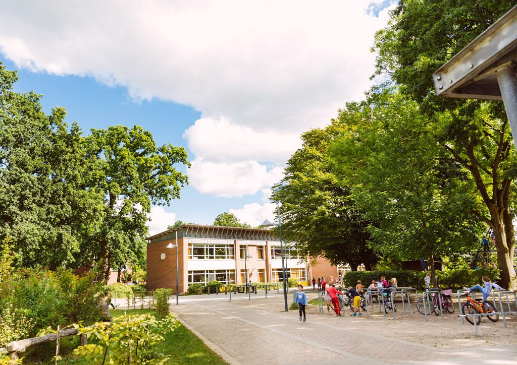 Das Bild zeigt einen Teil des Schulgebäudes der Schule Lehmkuhle. Davor befinden sich rechts die Fahrradständer mit ein paar Rädern und spielenden Kindern.