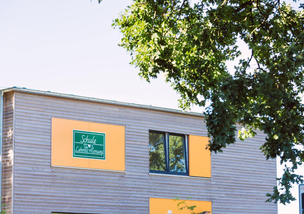 Das Bild zeigt einen oberen Teil des neuen Schulgebäudes der Schule Lehmkuhle. Das neue Gebäude hat eine Holzfassade und orange farbende Elemente. Auch das Logo der Schule ist dort zu sehen.