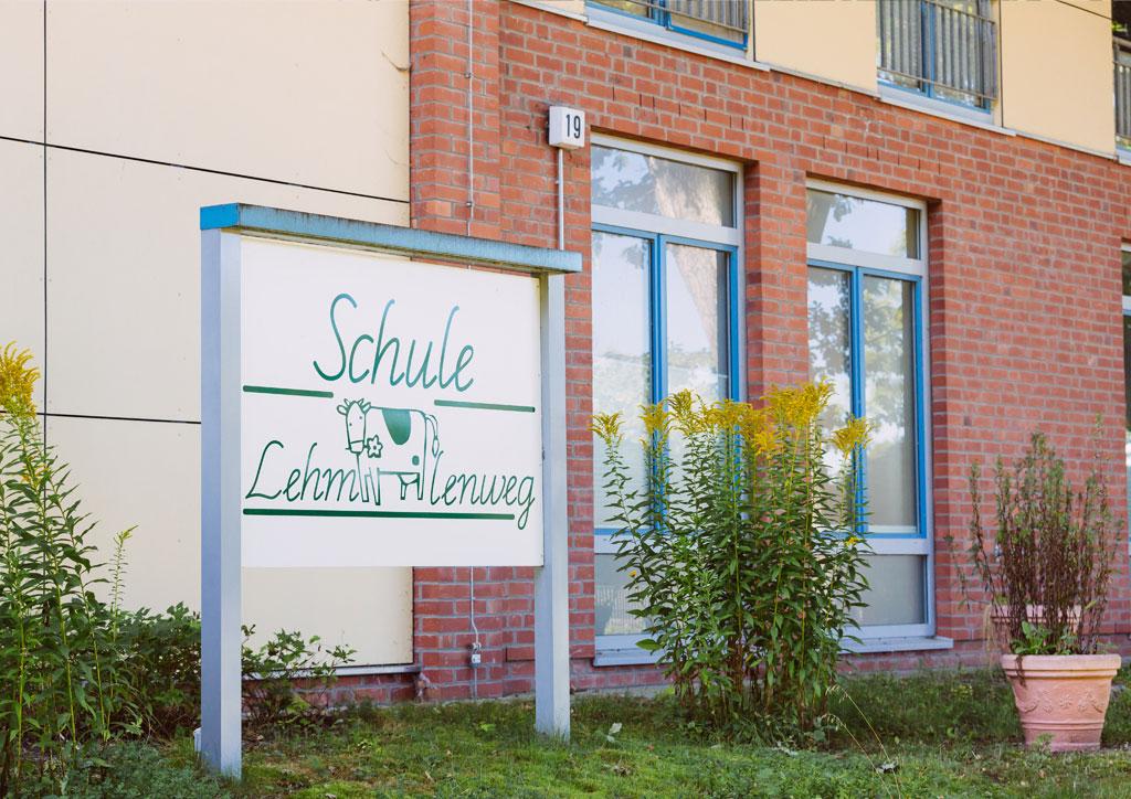 Das Bild zeigt das große Eingangsschild der Schule Lehmkuhle mit dem Kuh-Logo. In dem hinteren Gebäude befindet sich die Aula.