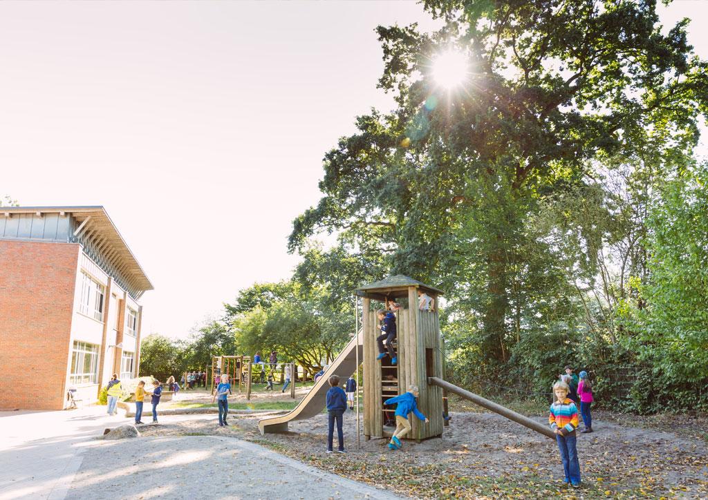 Das Bild zeigt den Holz-Rutschturm der Schule Lehmkuhle. Viele Kinder spielen dort. Dahinter befinden sich noch Kletterstangen.