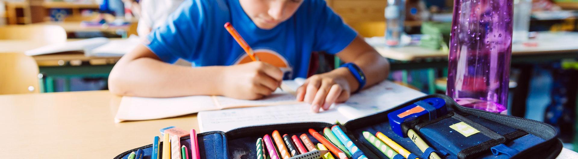 Ein schüler sitzt an einem Tisch und schreibt etwas in sein Heft.