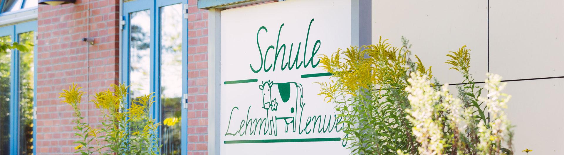 Das Bild zeigt das Schullogo auf einem großen Schild vor dem Schulgebäude der Schule Lehmkuhle.
