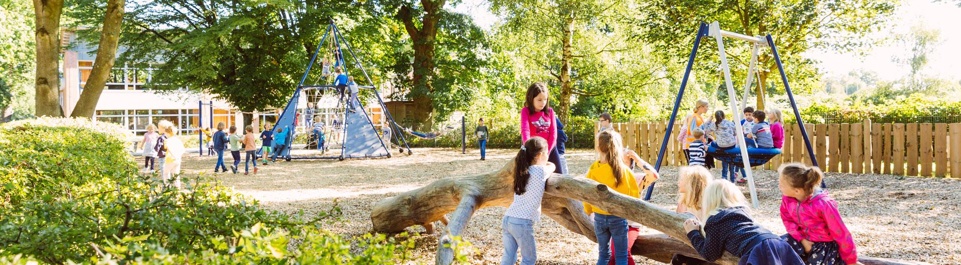 Viele Kinder spielen in der Sonne auf dem Schulhof