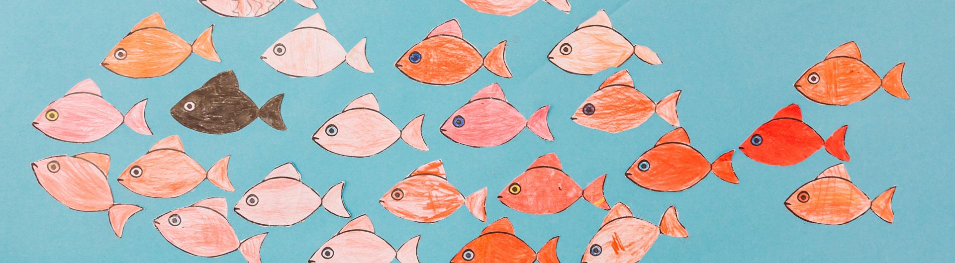 Viele Papierfische schwimmen zusammen in eine Richtung