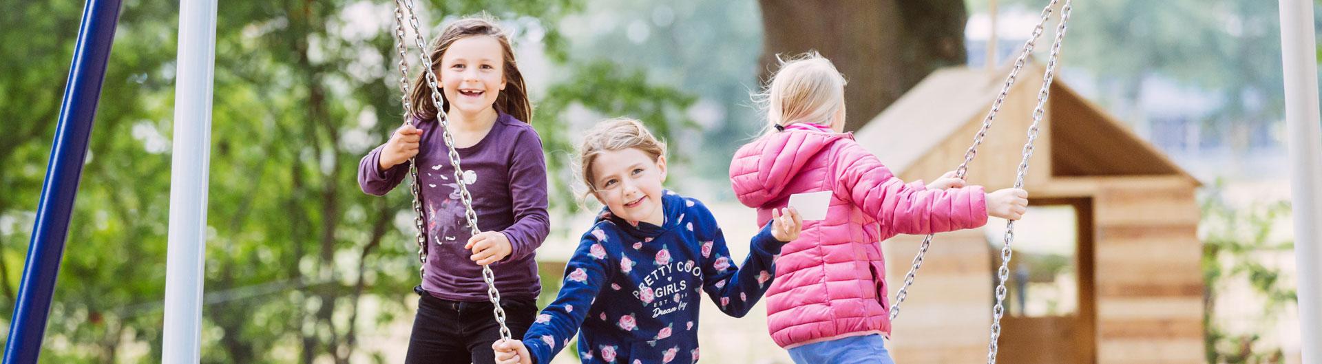 Das Bild zeigt 3 Mädchen, die in einer Nestschaukel spielen.