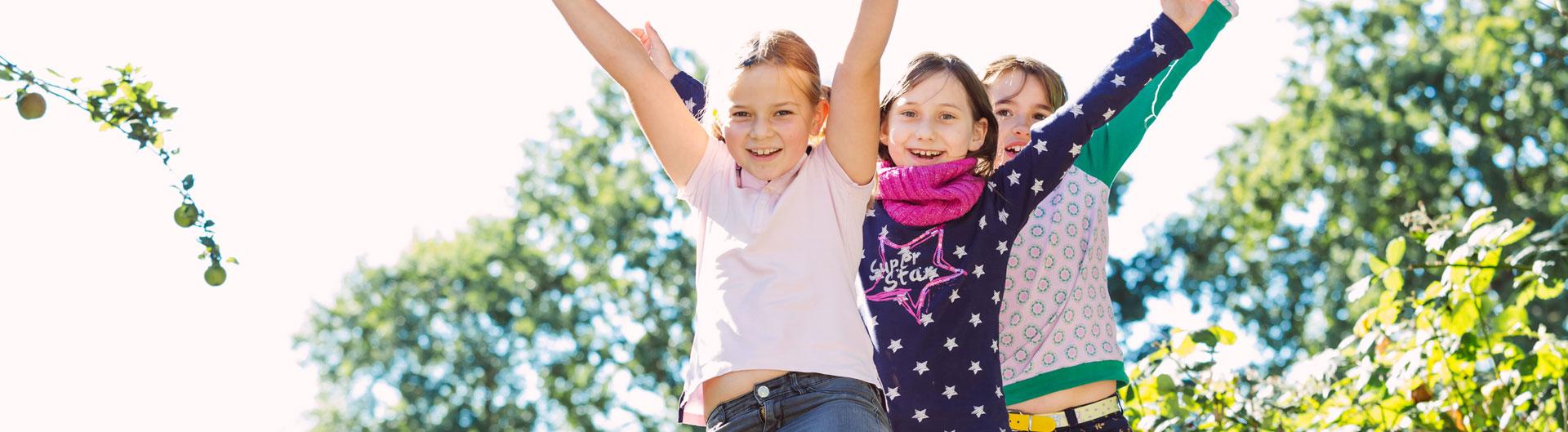 Drei Schülerinnen sitzen auf einem Spielhaus und strecken die Arme in die Höhe.