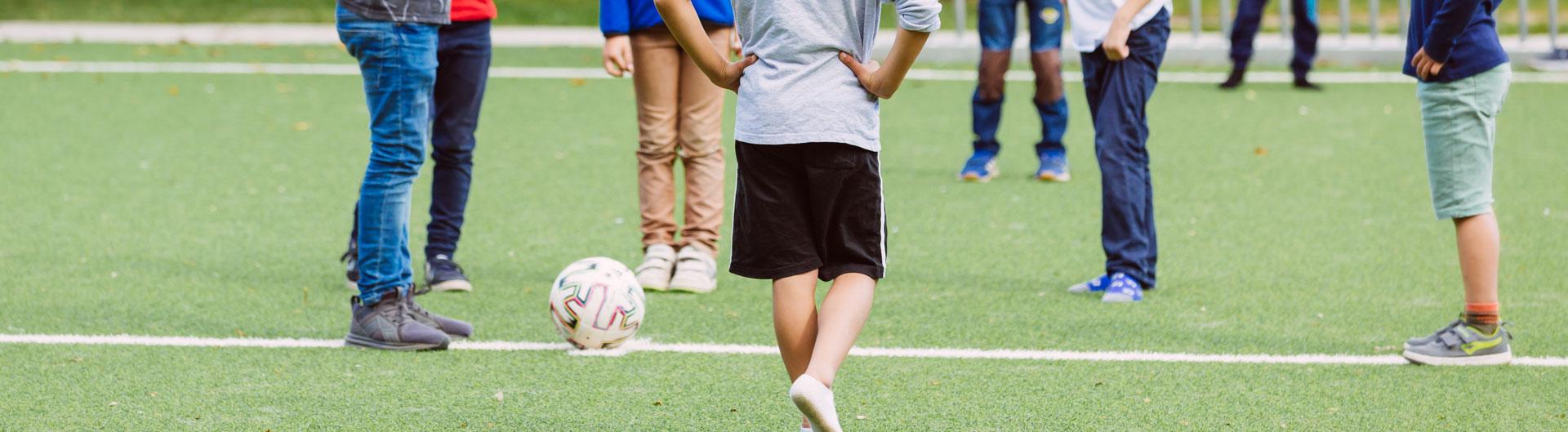 Viele Schüler stehen auf einem Fußballfeld. Man sieht nur die Beine und Füße.
