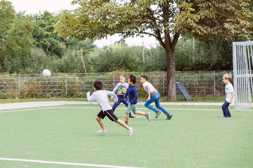 Das Bild zeigt einen Teil des Fußballplatzes der Schule Lehmkuhle. Dort spielen fünf Jungs Fußball.