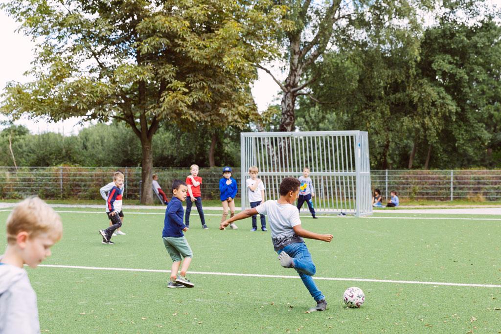 Das Bild zeigt einen Teil des Fußballplatzes der Schule Lehmkuhle. Dort spielen einige Jungs Fußball.