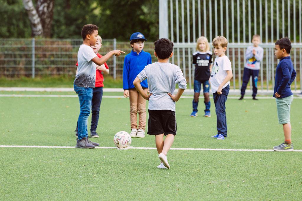 Das Bild zeigt einen Teil des Fußballplatzes der Schule Lehmkuhle. Dort spielen einige Jungs Fußball und es wird gerade diskutiert, wer den Einwurf macht.
