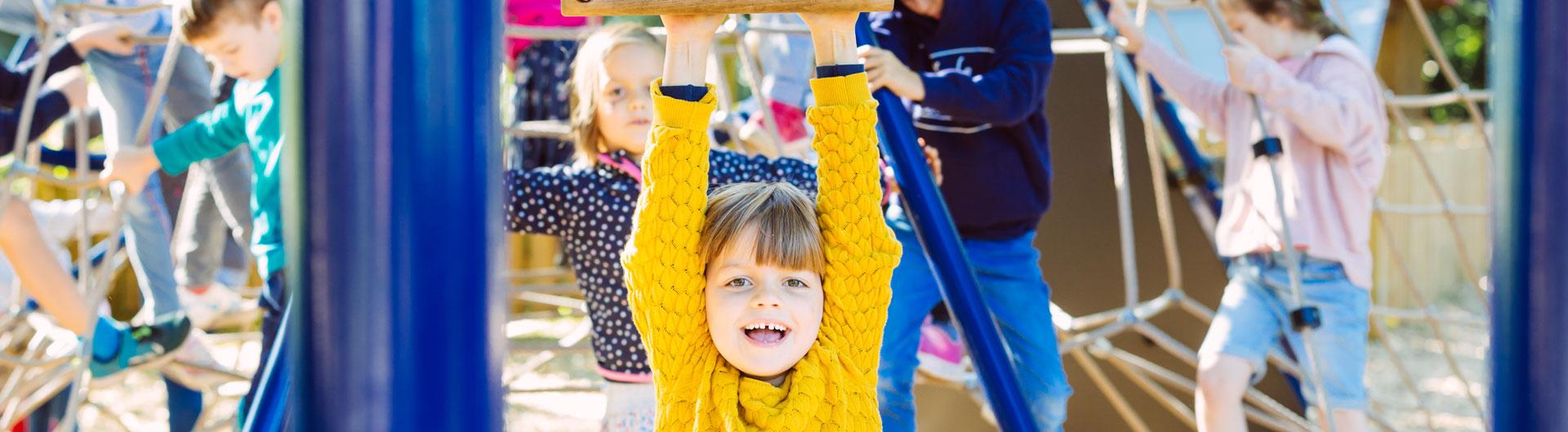 Eine Schülerin spielt in der Kletterspinne auf dem Schulhof