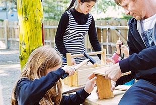 Das Bild zeigt zwei Kinder mit einem Betreuuer aus der GBS. Die Kinder basteln unter Anleitung etwas aus Holz.