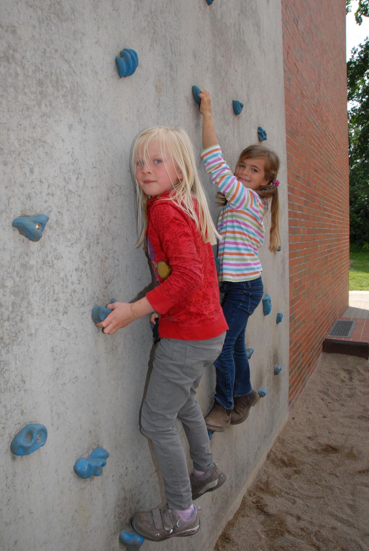 Zwei Mädchen klettern draußen am Schulgebäude die Kletterwand hoch.