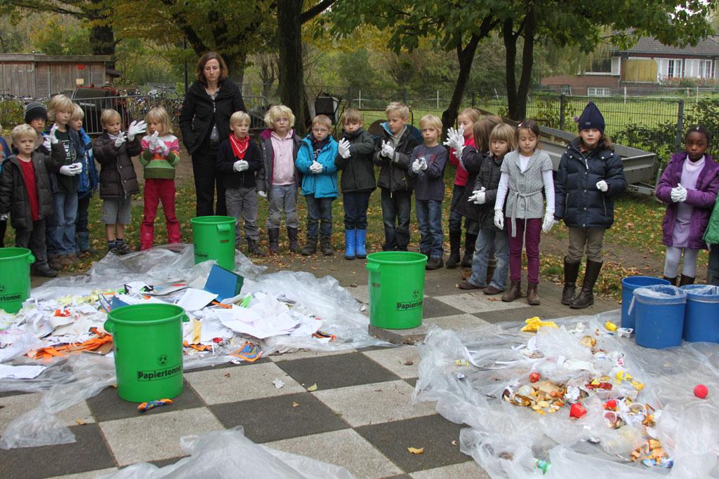 Eine Schülergruppe steht vor selbst gesammelten Bergen von Müll.